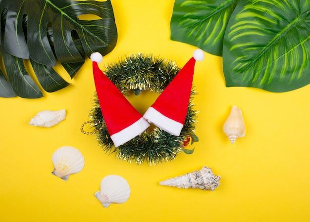 Weihnachtsmützen auf einem weihnachtskranz, tropischen blättern und muscheln