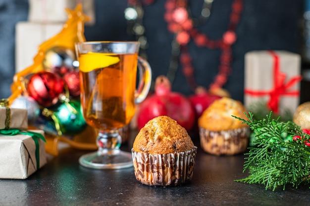 Weihnachtsmuffins mit dekorationen auf schwarzem tisch
