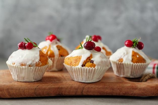 Weihnachtsmuffins mit preiselbeeren und rosmarin serviert auf holzbrett.