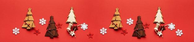 Weihnachtsmuster aus hölzernen weihnachtstannenbaumspielzeugen, schneeflocken und sternen auf rot. flach liegen. banner. attrappe, lehrmodell, simulation.