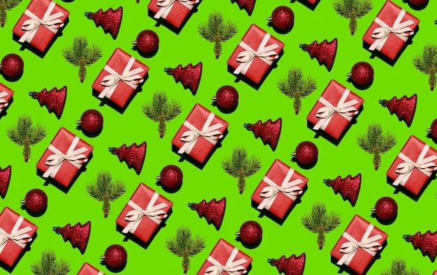 Weihnachtsmuster aus tannenzweigen in rotem papier und weihnachtskugeln auf grünem hintergrund chris...