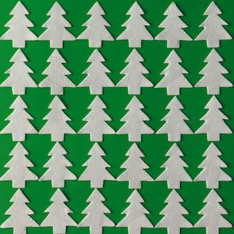 Weihnachtsmuster gemacht von weißen weihnachtsbäumen auf grüner wand. flach liegen. urlaubskonzept.