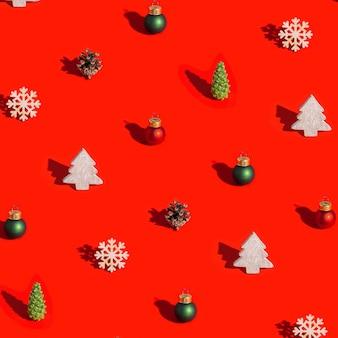 Weihnachtsmuster mit natürlichen dekorationen holzspielzeug tannenzapfen mit dunklem schatten auf rot