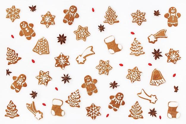 Weihnachtsmuster von lebkuchenplätzchen und gewürzen auf weißem hintergrund. flach liegen.