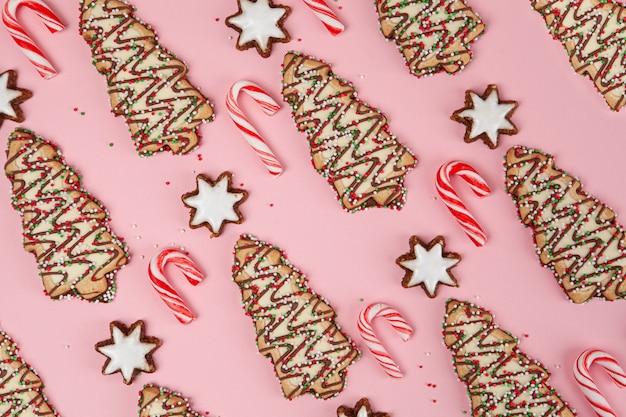 Weihnachtsnachtischhintergrundmuster - zuckerstangen mit sternen und weihnachtsbäumen auf rosa, draufsicht
