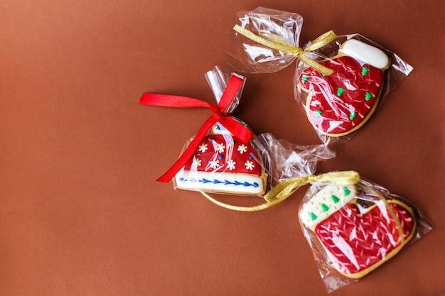 Weihnachtsneujahrsfeiertagshintergrund, rote lebkuchenplätzchen und kegel auf dunkelroter tabelle. kopieren sie platz