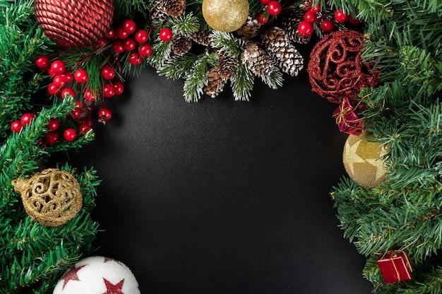 Weihnachtsneujahrskomposition auf schwarzem hintergrund. tannenzweige, weihnachtsdekoration. flache lage, draufsicht, kopierraum.