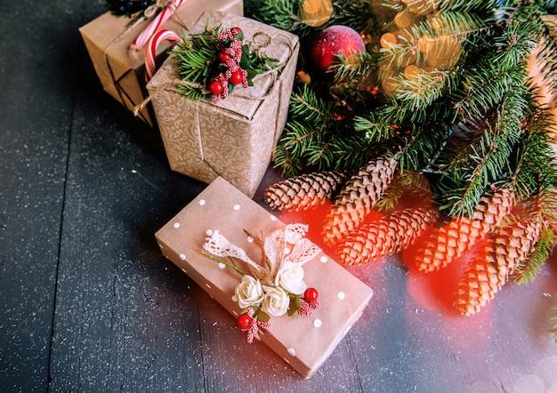 Weihnachtsoberfläche mit dekorationen und geschenkboxen auf hölzernem brett