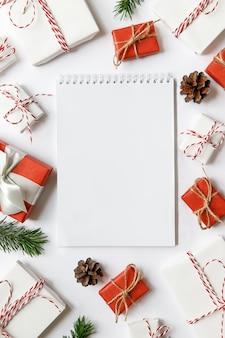 Weihnachtsoberfläche mit leerem notizbuch, rot und weiß verpackten geschenkboxen mit band, tannenzweigen, zapfen auf weißer oberfläche. flach liegen. platz für text.