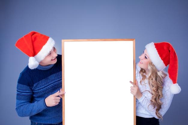 Weihnachtspaar, das weißes brett mit leerem kopienraum hält