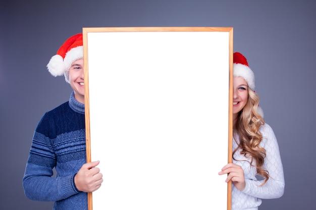 Weihnachtspaare, die weißes brett mit leerem kopienraum über blauem hintergrund halten. konzept der werbung für den einkaufsverkauf der neuen saison