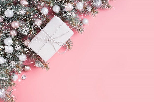 Weihnachtspastellzusammensetzung mit weißem geschenk auf rosa. weihnachtsfeld mit copyspace. sicht von oben.