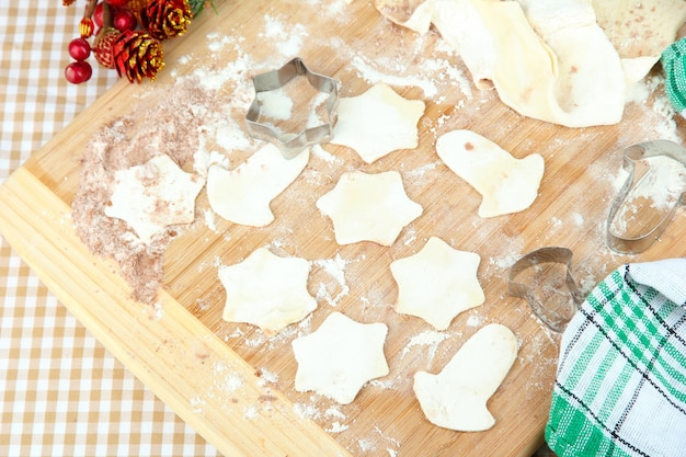 Weihnachtsplätzchen auf holzbrett auf tischdecke hintergrund backen