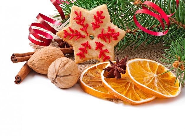 Weihnachtsplätzchen, -gewürze und -fichtenzweige lokalisiert auf weißem hintergrund