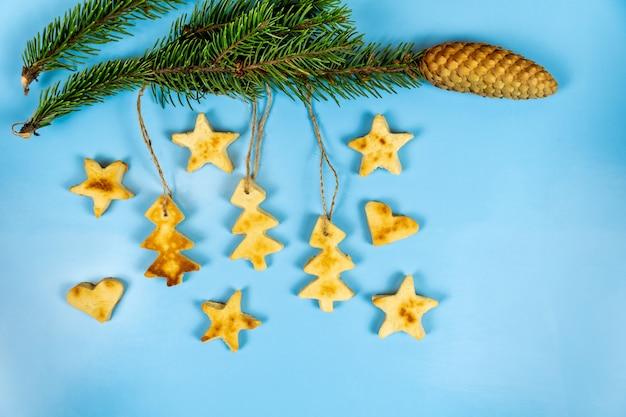 Weihnachtsplätzchen hängen an einem tannenzweig auf einem blau.
