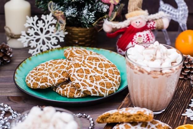 Weihnachtsplätzchen in einer platte und in einem heißen kakao mit eibischen in den gläsern auf dem tisch mit weihnachtsdekorationen