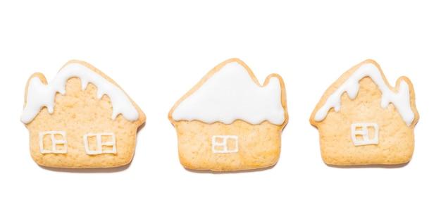Weihnachtsplätzchen in form von häusern auf lokalisiertem weißem hintergrund