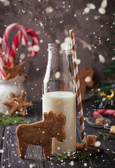 Weihnachtsplätzchen in form von rehen und milch. tiefenschärfe, schnee-effekt, getönt