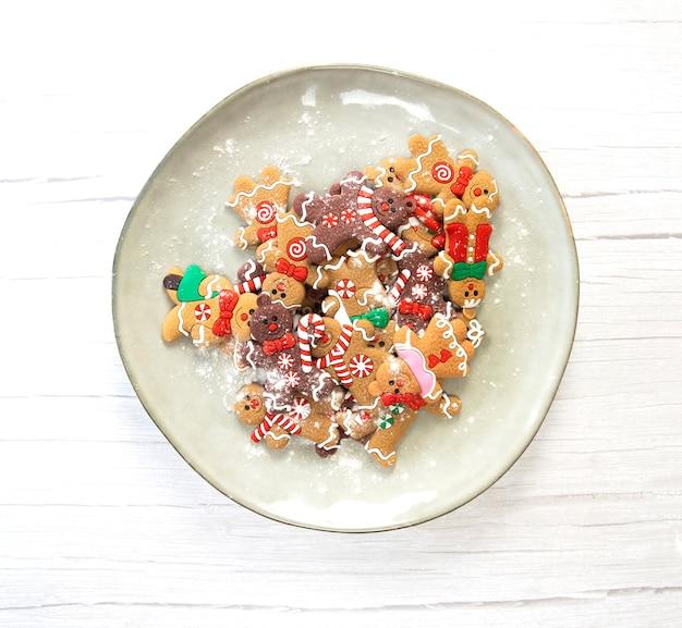 Weihnachtsplätzchen, lebkuchenmannplätzchen mit puderzucker auf natürlichem teller, weiße hölzerne hintergrundtextur, hausgemachte draufsicht