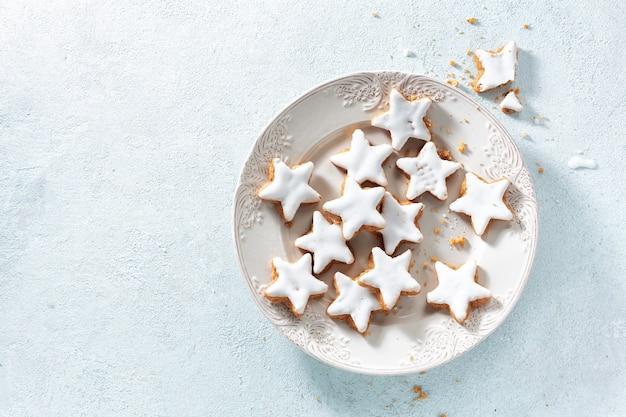 Weihnachtsplätzchen mit glasur auf weißem teller auf hellblau.