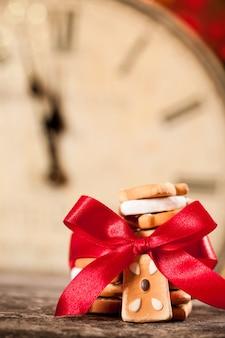 Weihnachtsplätzchen mit roter schleife gegen alte uhr