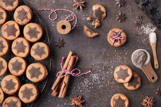 Weihnachtsplätzchen mit schokoladensternmuster auf abkühlendem gestell mit gewürzen