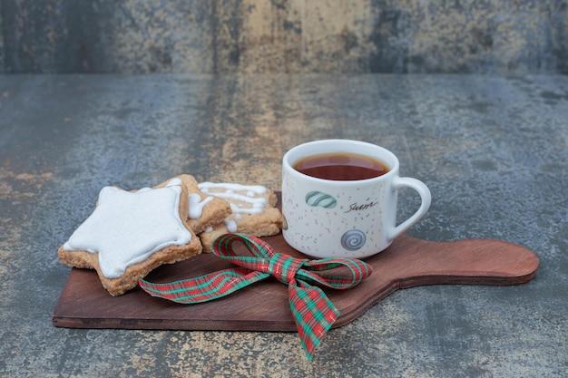 Weihnachtsplätzchen mit tasse tee auf holzbrett