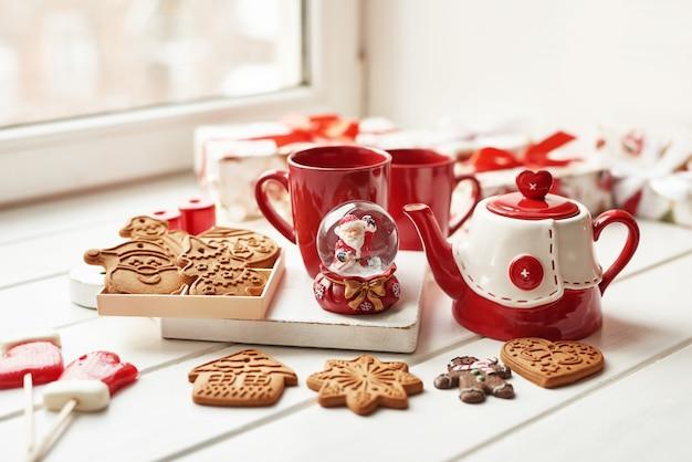 Weihnachtsplätzchen und becher heißer tee, weihnachtszeit. weihnachtslebkuchen, süßigkeit, kaffee in der roten schale auf holztisch auf eisiger wintertagesfenstertabelle. zuhause gemütliche ferien. postkarte vorlage