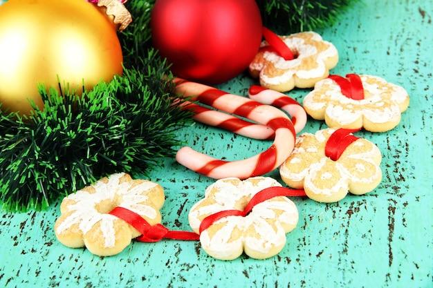 Weihnachtsplätzchen und dekorationen auf farbigem holzhintergrund