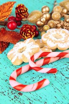 Weihnachtsplätzchen und dekorationen auf farbigem holztisch