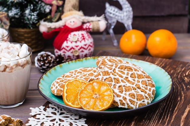 Weihnachtsplätzchen und getrocknete mandarinenscheiben in einer platte und in einem heißen kakao mit eibischen in den gläsern auf tabelle mit weihnachtsdekorationen