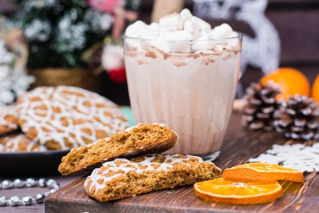 Weihnachtsplätzchen und heißer kakao mit eibischen in den gläsern auf dem tisch mit weihnachtsdekorationen