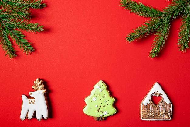 Weihnachtsplätzchen und tannenzweige auf rotem grund