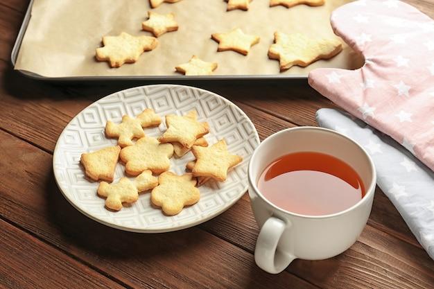 Weihnachtsplätzchen und tasse tee auf holztisch