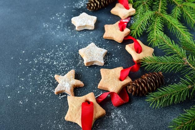 Weihnachtsplätzchen verziert mit einem roten band mit einem bogen und einem kleinen zweig