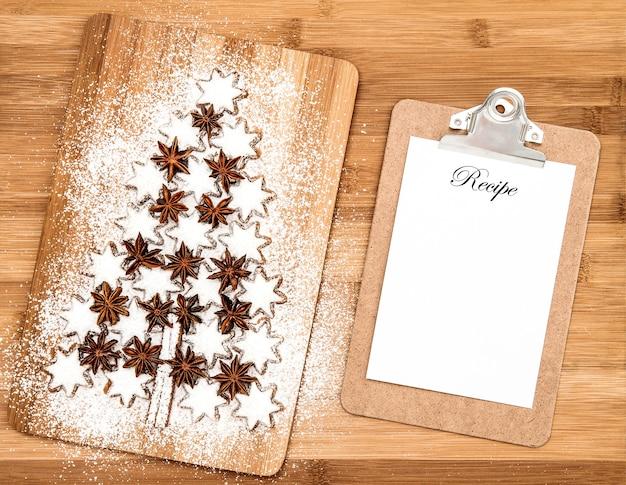 Weihnachtsplätzchen-zimtsterne und anschlagbrett für rezept auf hölzernem hintergrund. plätzchen in weihnachtsbaumform