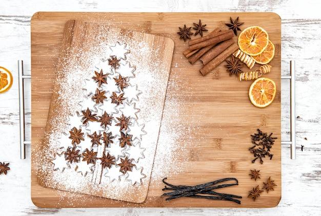 Weihnachtsplätzchen-zimtsterne und -gewürze auf hölzernem hintergrund. vanilleschoten, nelken, sternanis und zimt. festliches essen