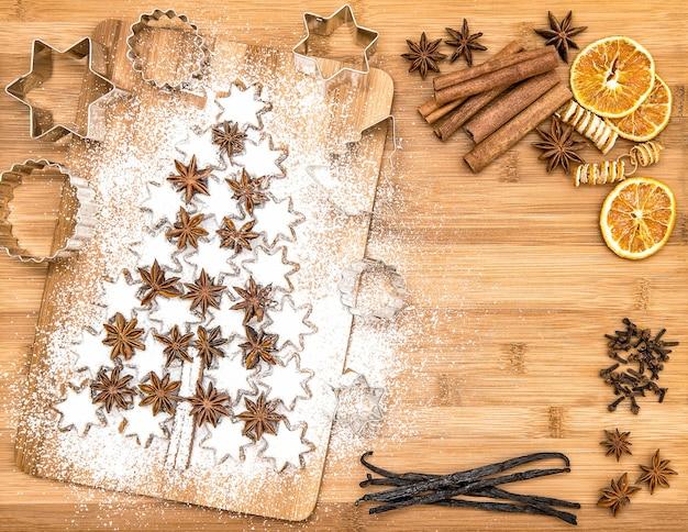 Weihnachtsplätzchen-zimtsterne und -gewürze auf hölzernem hintergrund. vanilleschoten, nelken, sternanis und zimt