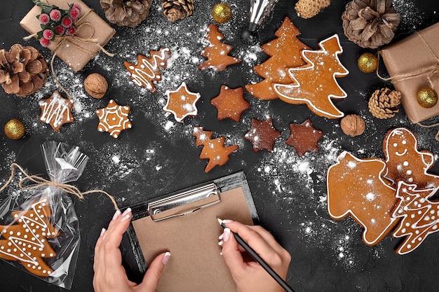 Weihnachtsplätzchenbaum mit stern-ausstecher-lebkuchen-neujahrsgebäck, dekoriert mit seilschleife und form zum ausschneiden von keksen auf schwarzem tisch. festliches süßes gebäck leckeres essen