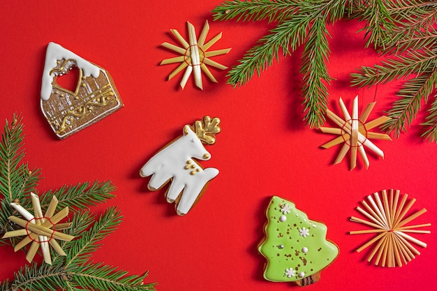 Weihnachtsplätzchendekorationen und tannenbaumzweige auf rotem hintergrund