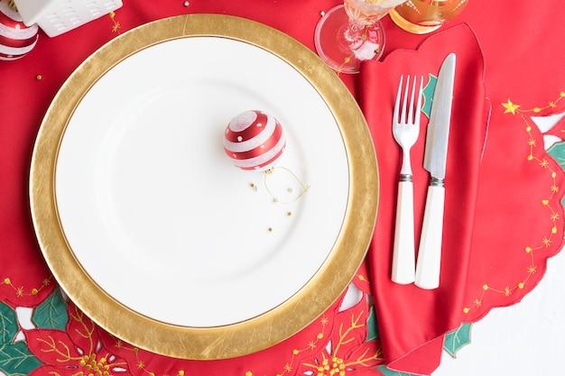 Weihnachtsportion - leere weiße und goldene teller mit messer und gabel