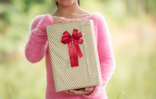 Weihnachtsporträt des glücklichen lächelnden kindes des kleinen mädchens mit geschenkbox nahe einem grünen zweigbaum. grüne blätter bokeh unscharf hintergrund aus dem naturwald.