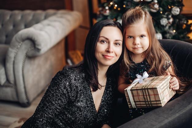 Weihnachtsporträt des mutter- und tochtermädchenkindes, das festliches geschenk, glückliches mutterschaftskonzept hält.