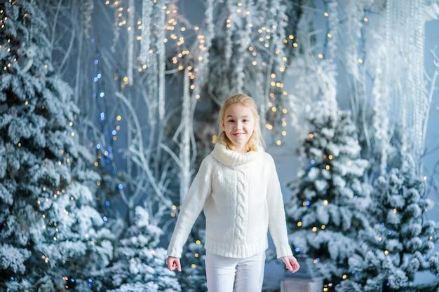 Weihnachtsporträt des ndoor studios des glücklichen blonden kindermädchens, schneebedeckter winter verzierte baum