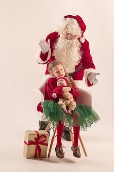 Weihnachtsporträt des niedlichen kleinen neugeborenen, hübsche jugendlich schwester, gekleidet in weihnachtskleidung und weihnachtsmann mit geschenkbox