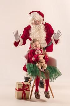 Weihnachtsporträt des niedlichen kleinen neugeborenen mädchens, der hübschen jugendlich schwester, gekleidet in weihnachtskleidung und mann, der weihnachtsmannkostüm und -hut, studioaufnahme, winterzeit trägt. das weihnachts-, feiertagskonzept