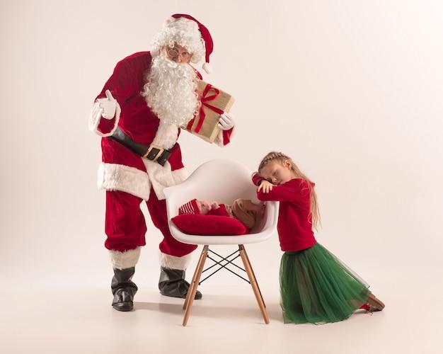 Weihnachtsporträt des niedlichen kleinen neugeborenen mädchens, der hübschen jugendlich schwester, gekleidet in weihnachtskleidung und weihnachtsmann