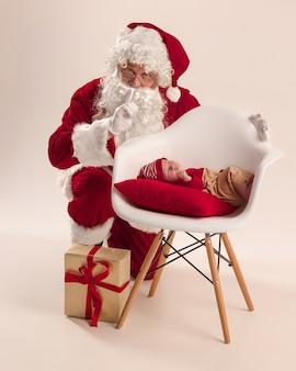 Weihnachtsporträt des niedlichen kleinen neugeborenen mädchens, gekleidet in weihnachtskleidung und mann, der weihnachtsmannkostüm und hut trägt