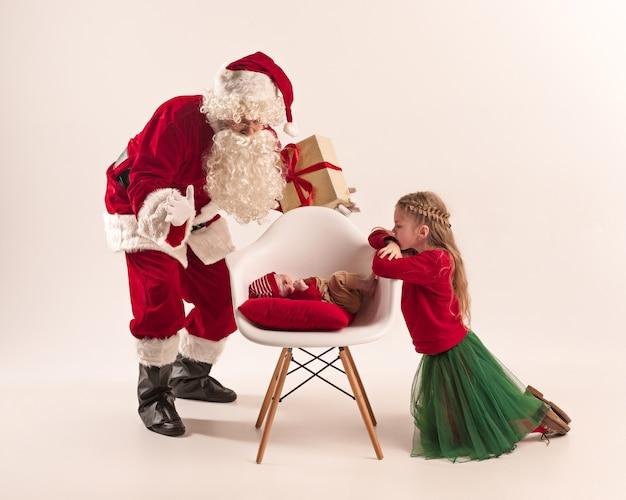 Weihnachtsporträt des niedlichen kleinen neugeborenen mädchens und der hübschen jugendlich schwester gekleidet in weihnachtskleidung und mann, der weihnachtsmannkostüm und -hut trägt