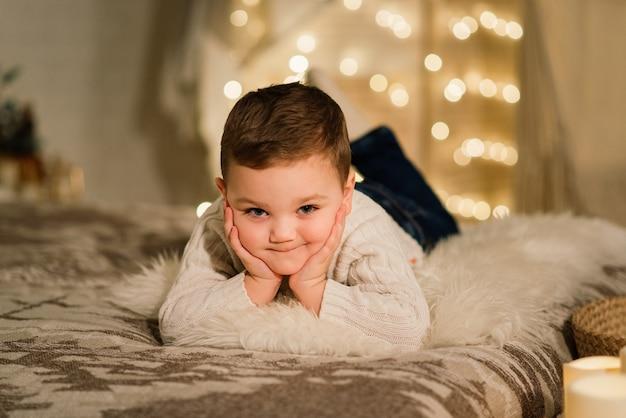 Weihnachtsporträt des süßen kleinen jungen, gekleidet in weihnachtskleidung, ein schuss, winterzeit